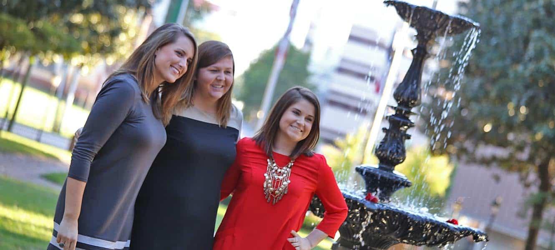 WPU alumni smiling by the Main Fountain.